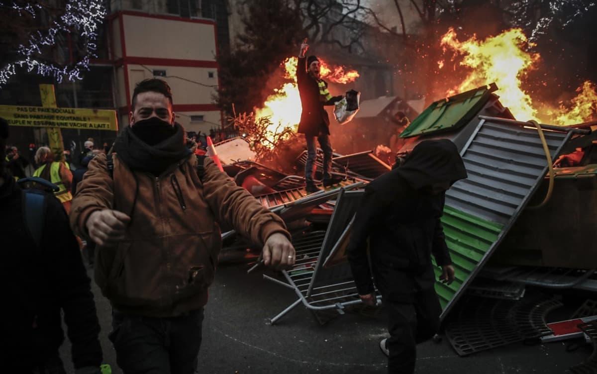 Kasvonsa peittäneitä mielenosoittajia heiluu palavien barrikadien luona.