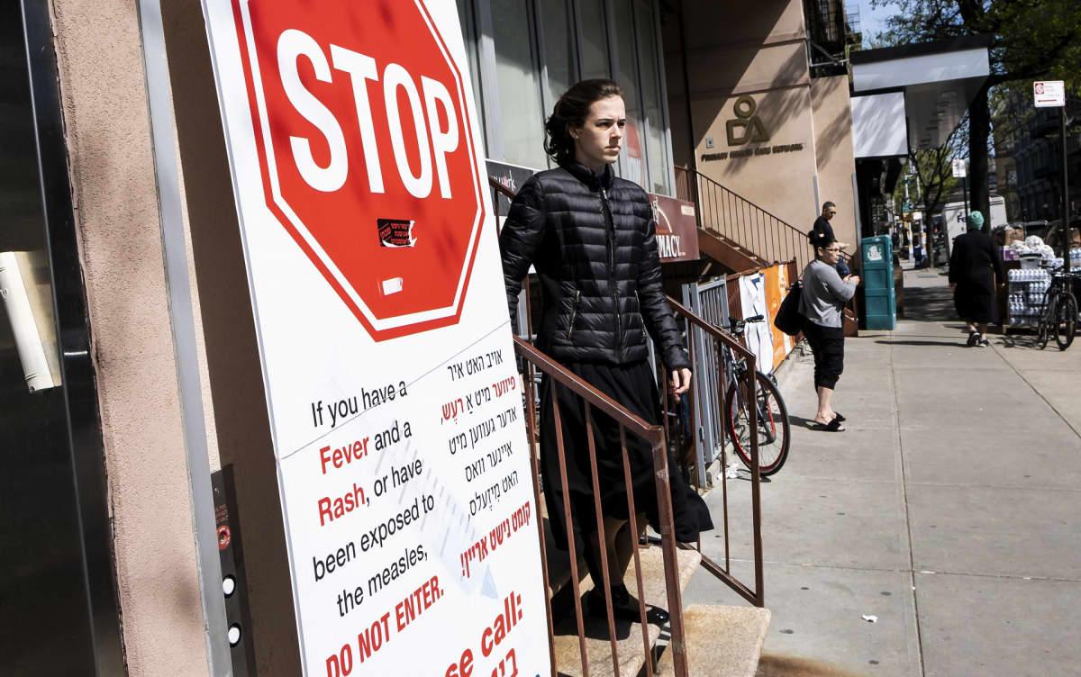 Kyltti New Yorkin Williamsburgissa varoitti torstaina astumasta sisään terveysklinikalle, jos oireita tuhkarokosta on.