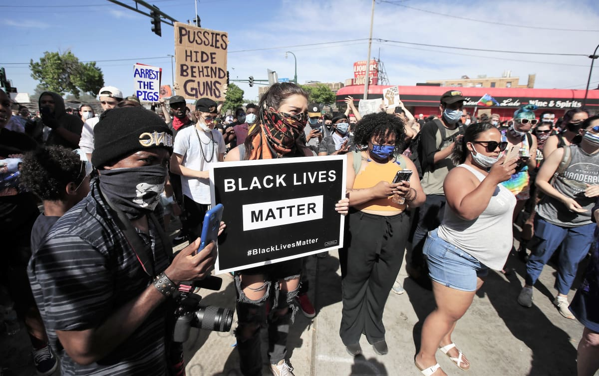 """Joukko mielenosoittajia seisoo kadulla. Kuvan keskellä nuorella naisella on kädessään kyltti, jossa lukee """"Black lives matter"""". Monilla on käsissään kännykät, joilla he kuvaavat. Monilla on myös kasvomaskit kasvoillaan."""