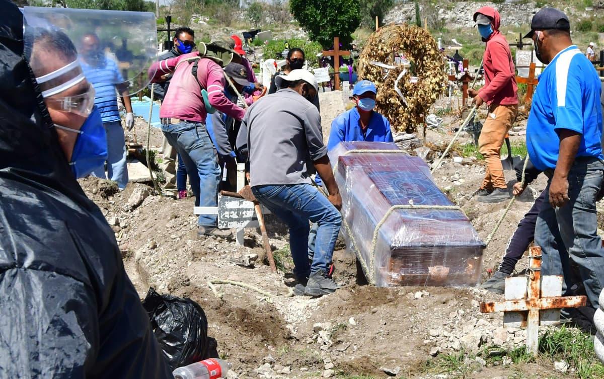 Surijat laskevat arkkua maahan Meksikossa.