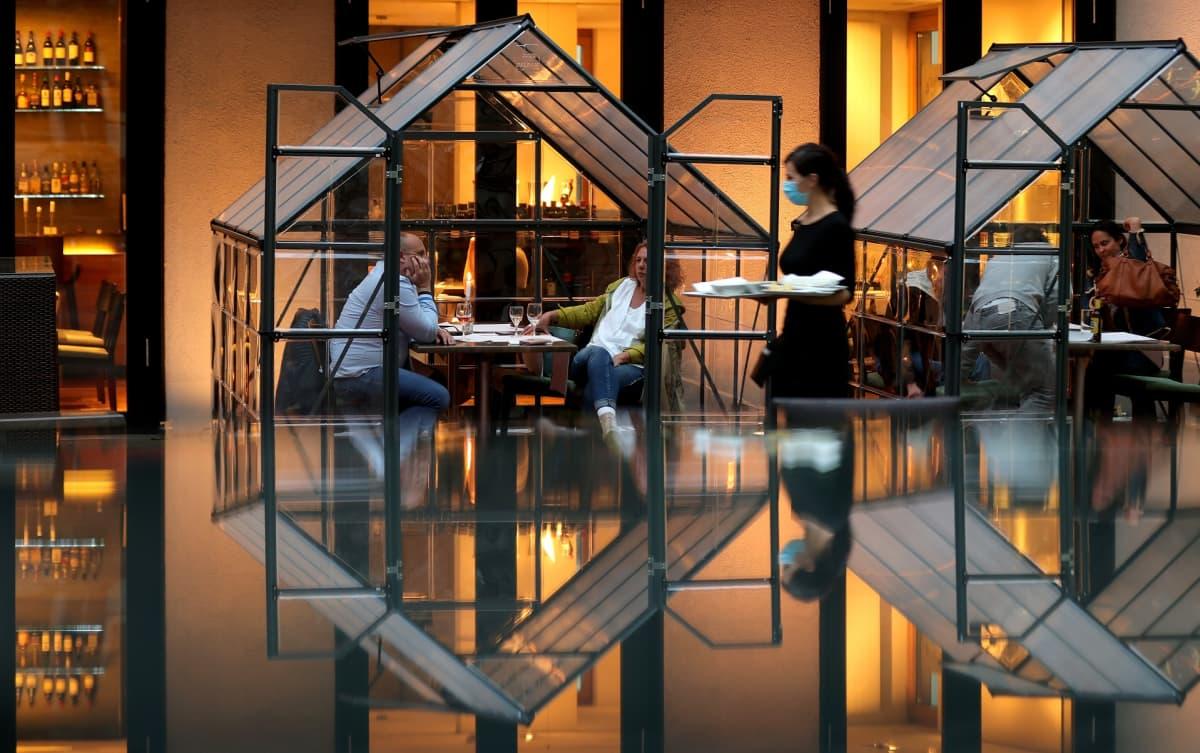 Ravintolan terassilla asiakkaat voivat eristäytyä omiin lasikoppeihinsa Hagenissa, Saksassa.