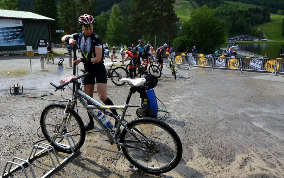 Painepesurilla pestään mutaisia pyöriä ja pyöräilijöitä