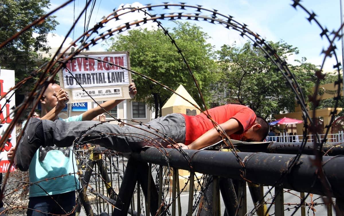 """Nuori mies makaa mahallaan kahden metallikaiteen päällä. Toinen mies pitelee kylttiä, jossa lukee: """"Ei enää koskaan sotatilalakia!"""""""