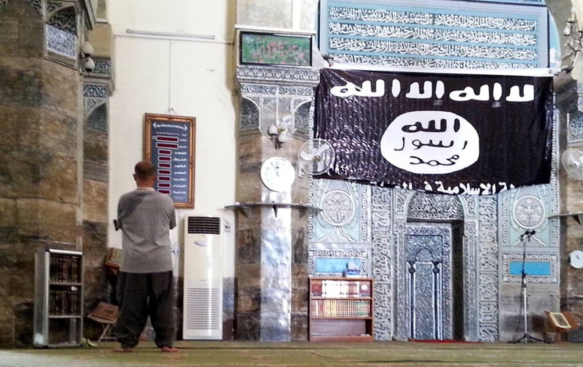 Mies rukoili Al-Noori Al-Kabeerin moskeijassa Mosulissa Irakissa, 9. heinäkuuta. Seinällä on islamilaisen valtion lippu.