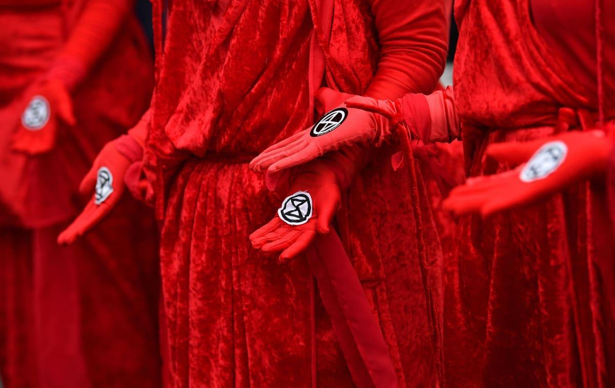 Puna-asuisilla ihmisillä on kirkkaanpunaiset, samettiset vaatteet. Käsissään heillä on mustavalkoisia, pyöreitä symbolikuvia.