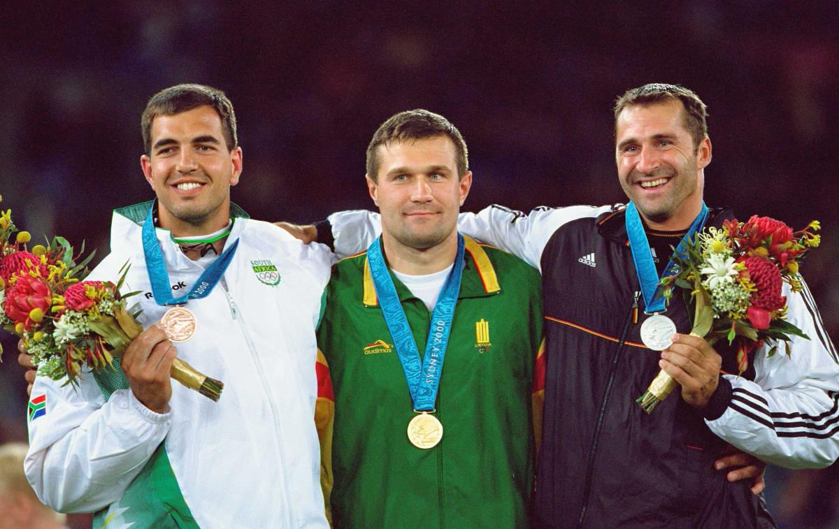 Frantz Kruger (vas.) saavutti kiekonheiton olympiapronssia Sydneyssä 2000. Kultaa kisassa kiskaisi Liettuan Virgilijus Alekna (kesk.) ja hopeaa Saksan Lars Riedel (oik.).