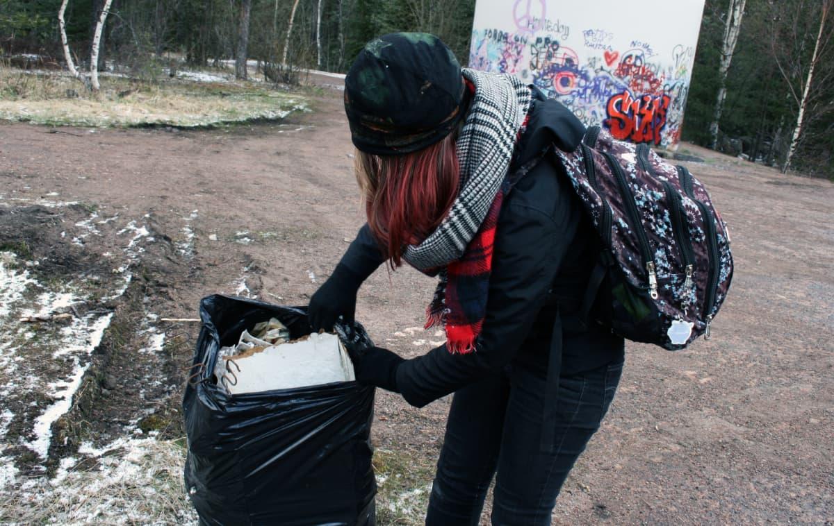 Tyttö kerää roskia.