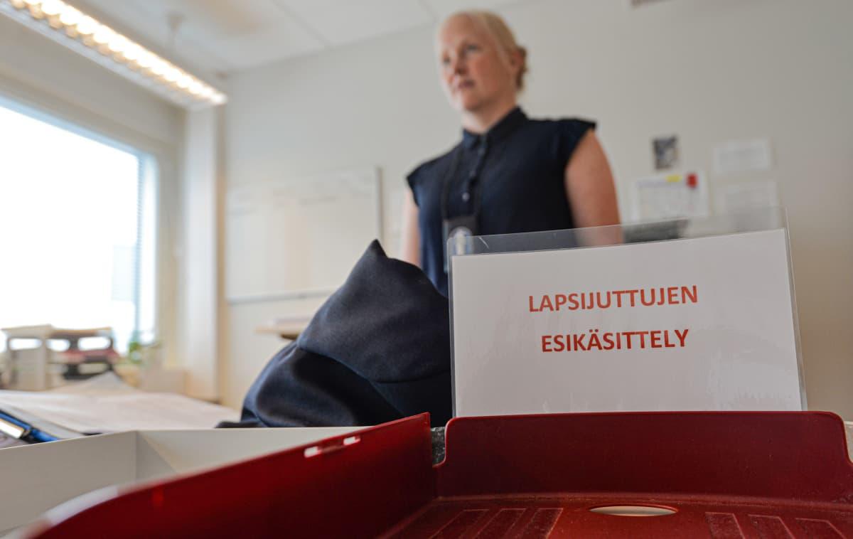 Poliisin työhuoneenssa asiakirja laatikko, jossa kyltti. Lapsijuttujen esikäsittely.