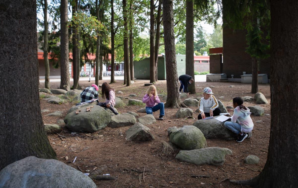 Kolmannen luokan oppilaita matematiikan tunnilla koulun pihalla.