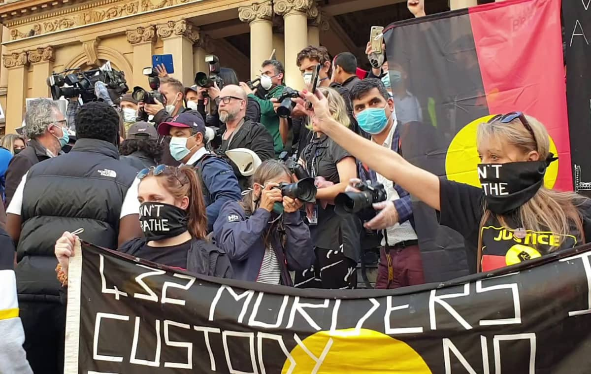 Ihmisjoukko lippujen kanssa kaupungintalon portailla.