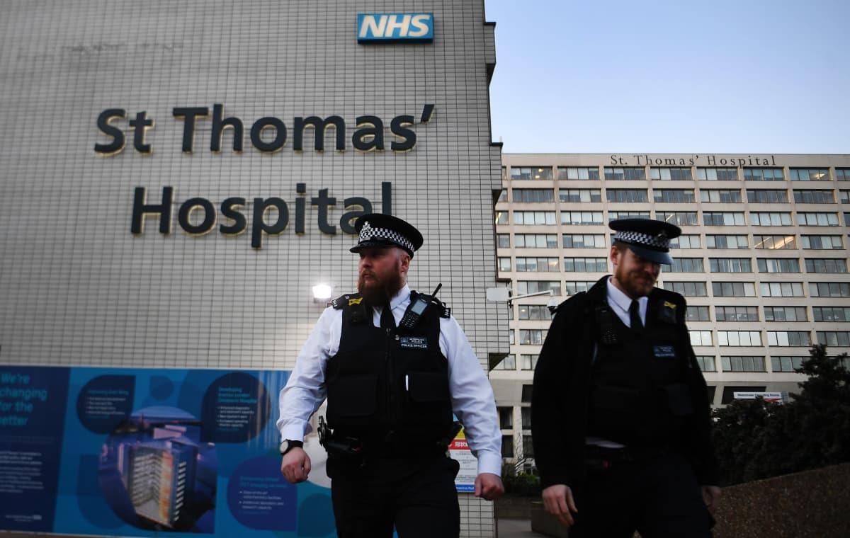 Kaksi poliisia sairaalarakennuksen edessä