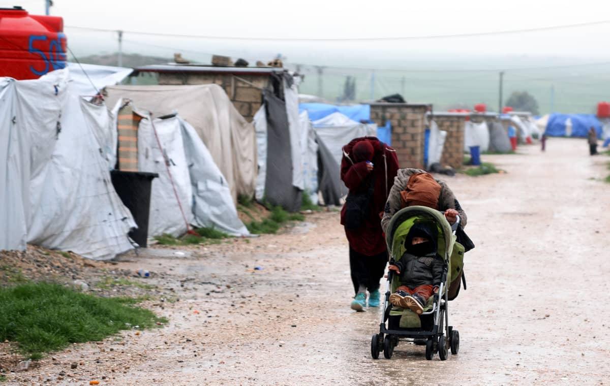 Nainen työntää lasta pyörätuolissa. Ympärillä on telttoja ja pieniä tiilirakennuksia.