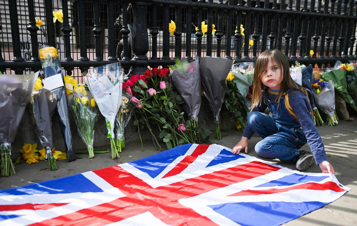 Lapsi levittää Union Jackin lipun Buckinghamin palatsin porttien eteen.