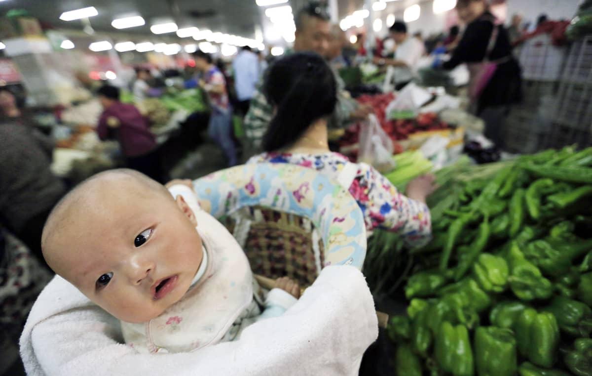 nainen kantaa vauvaa selässään