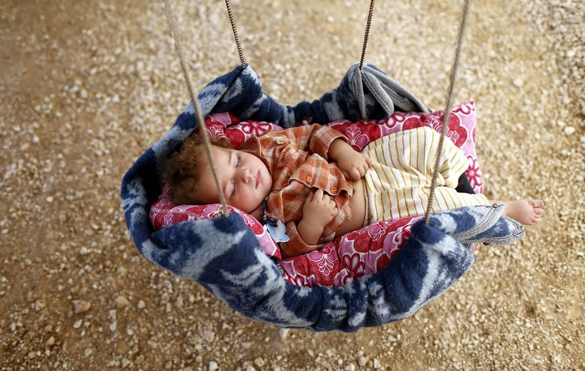 Syyrialainen taapero nukkui itsetehdyssä kehdossa teltassa pakolaisleirillä Surucin alueella, Turkissa 1. lokakuuta 2014.