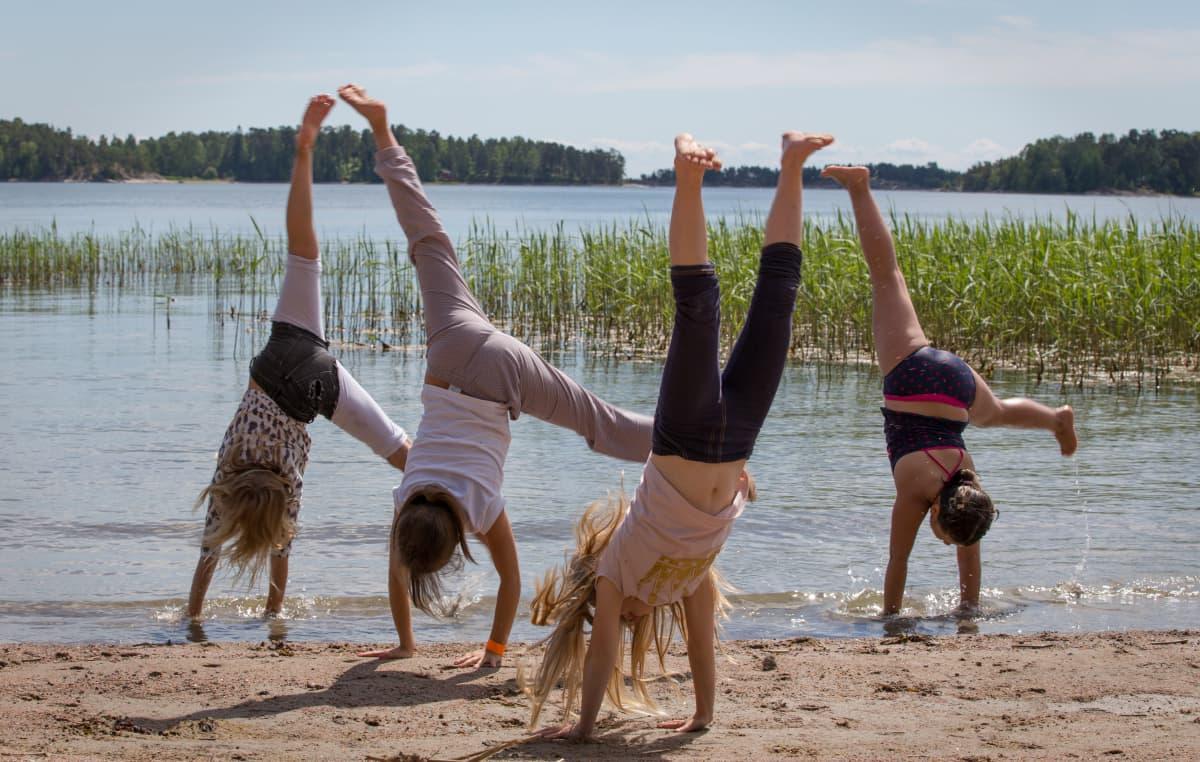 Anonyymejä lapsia tekemässä kärrynpyöriä rannalla kesälomalla aurinkoisella säällä.