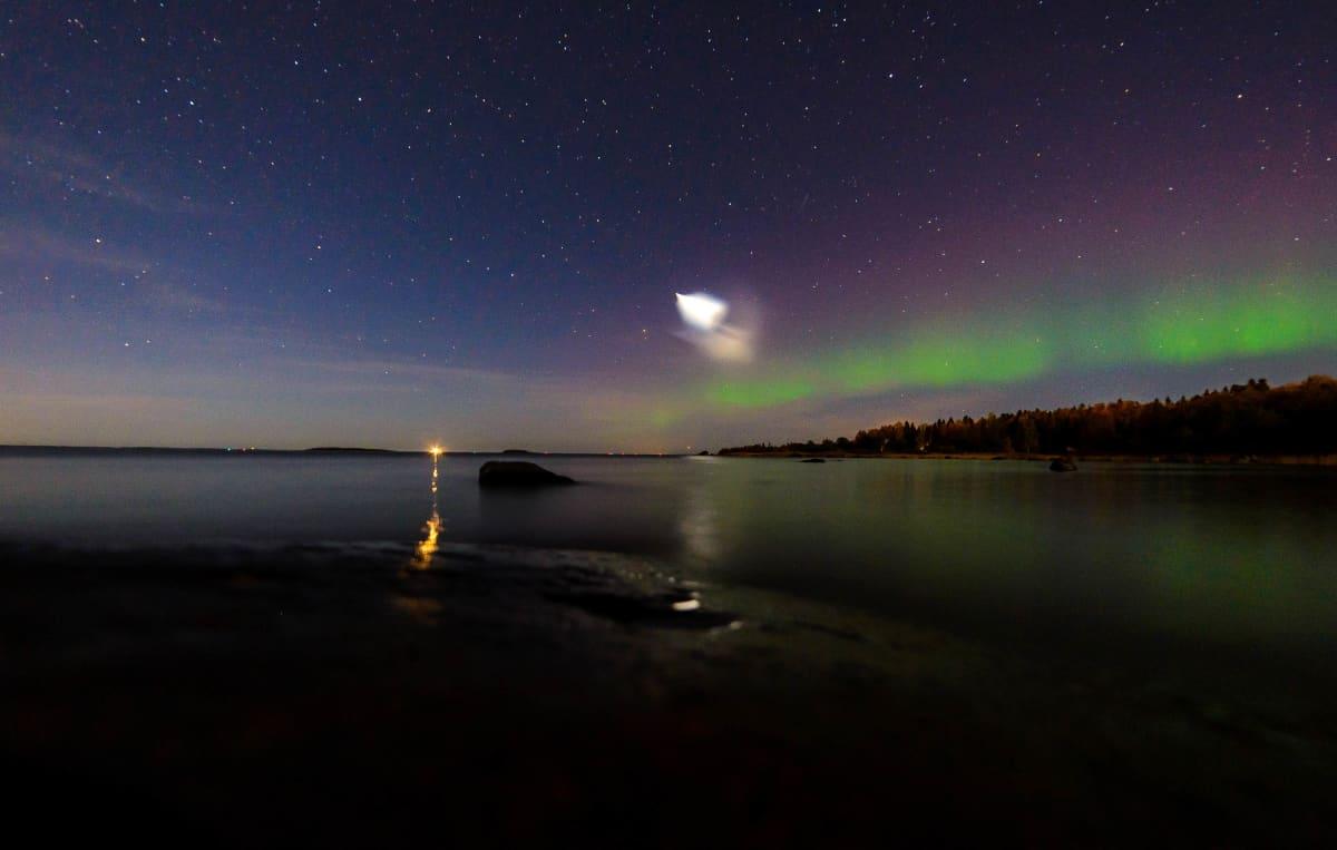 Tumma yötaivas, jossa tähtiä ja vihreät revontulet sekä kirkas valopallo keskellä kuvaa.