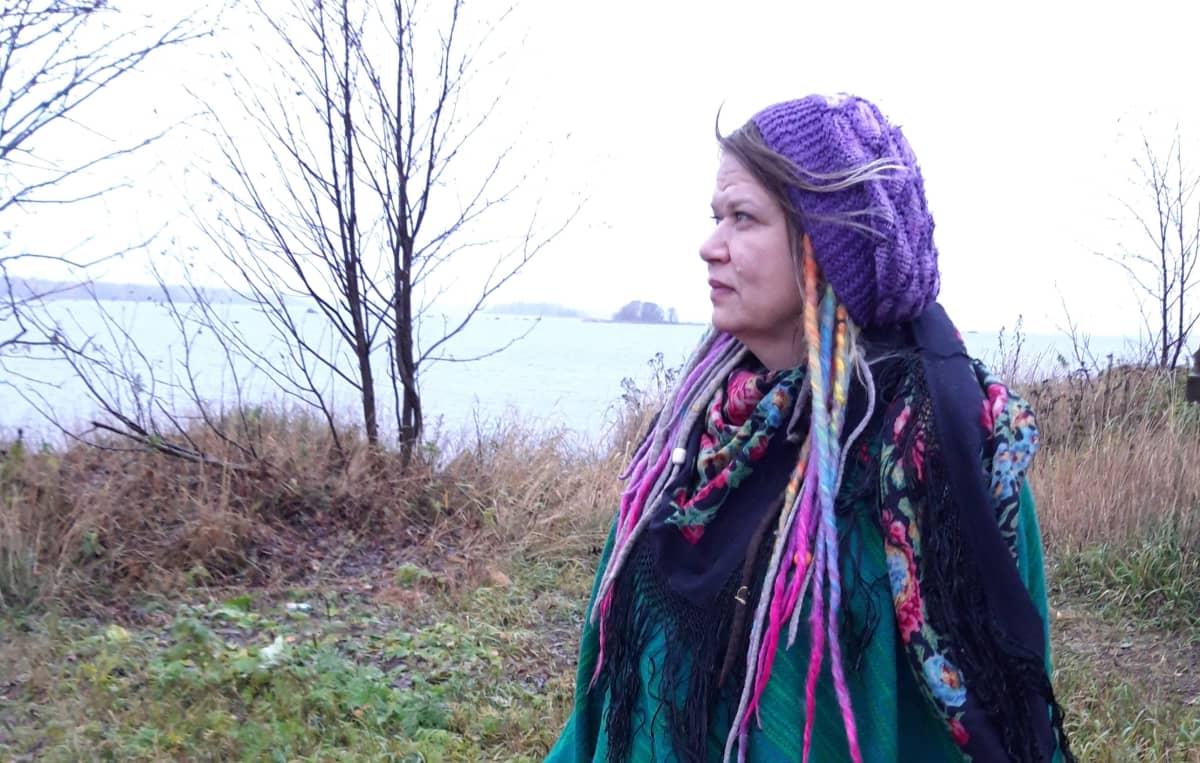 Nainen seisoo rannalla.