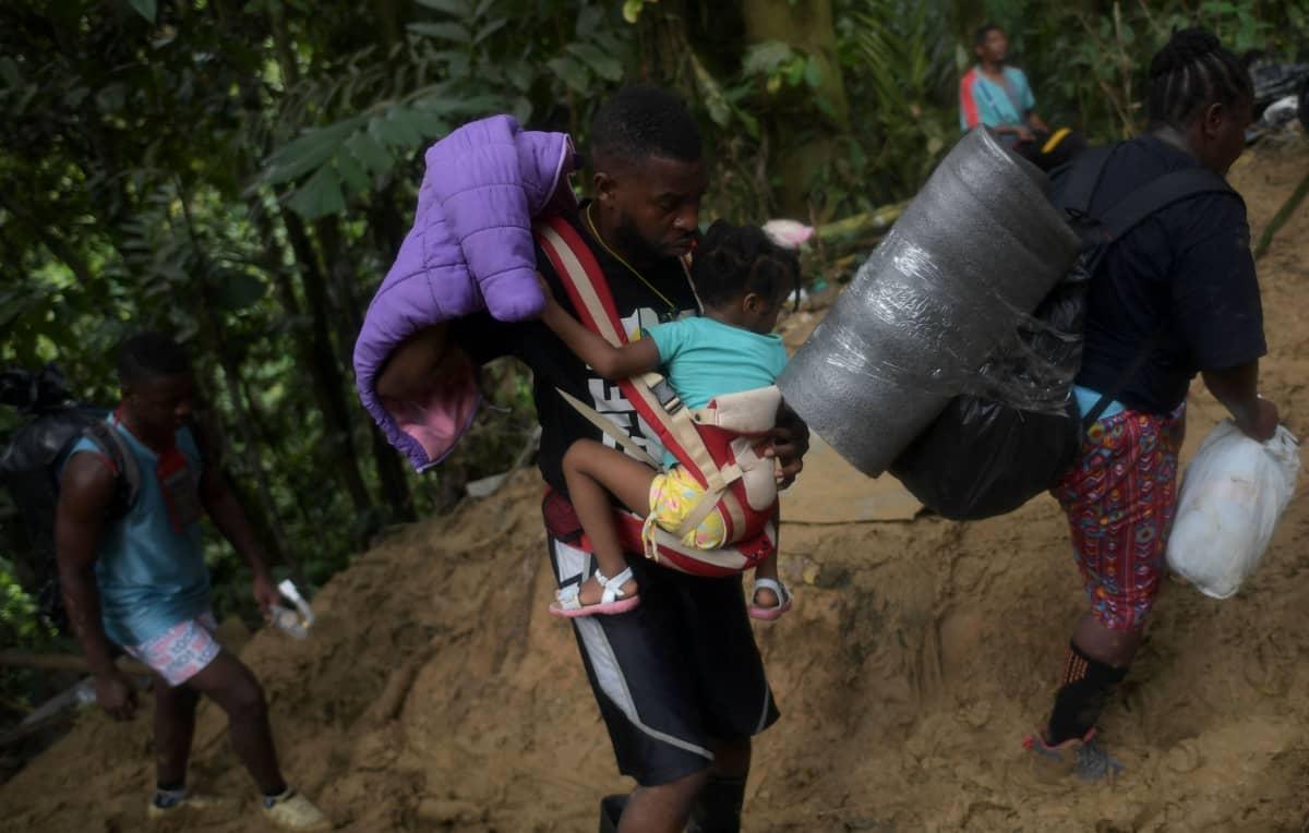 Mustaihoisia ihmisiä kävelemässä metsässä. He kantavat paljon tavaroita, mies keskellä kuvaa kantaa pientä lasta.