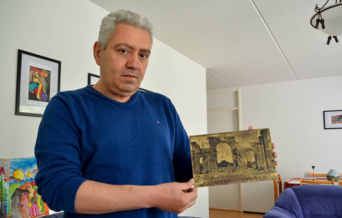 Asad Alkhateb Hassan esittelee Syyriassa tekemäänsä taulua.