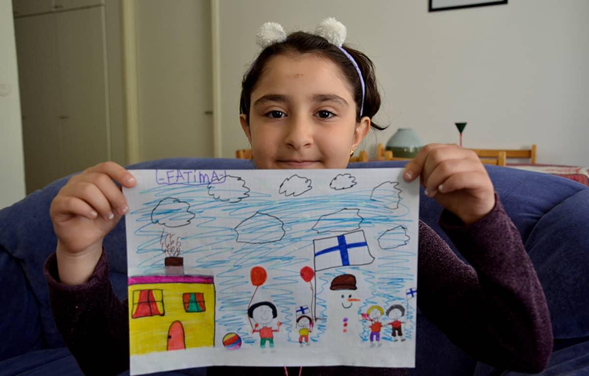 Fatima esittelee perheestään tekemäänsä piirosta.