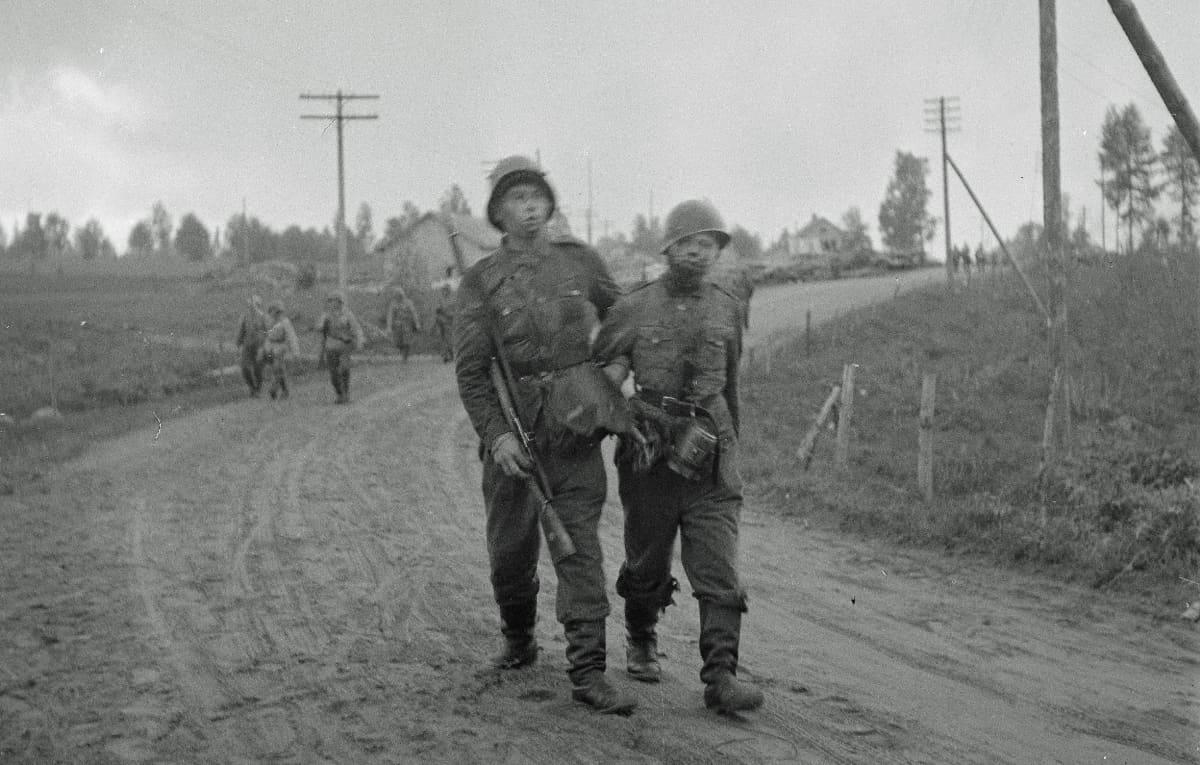 Väsyneet sotilaat kulkevat käsikynkkää