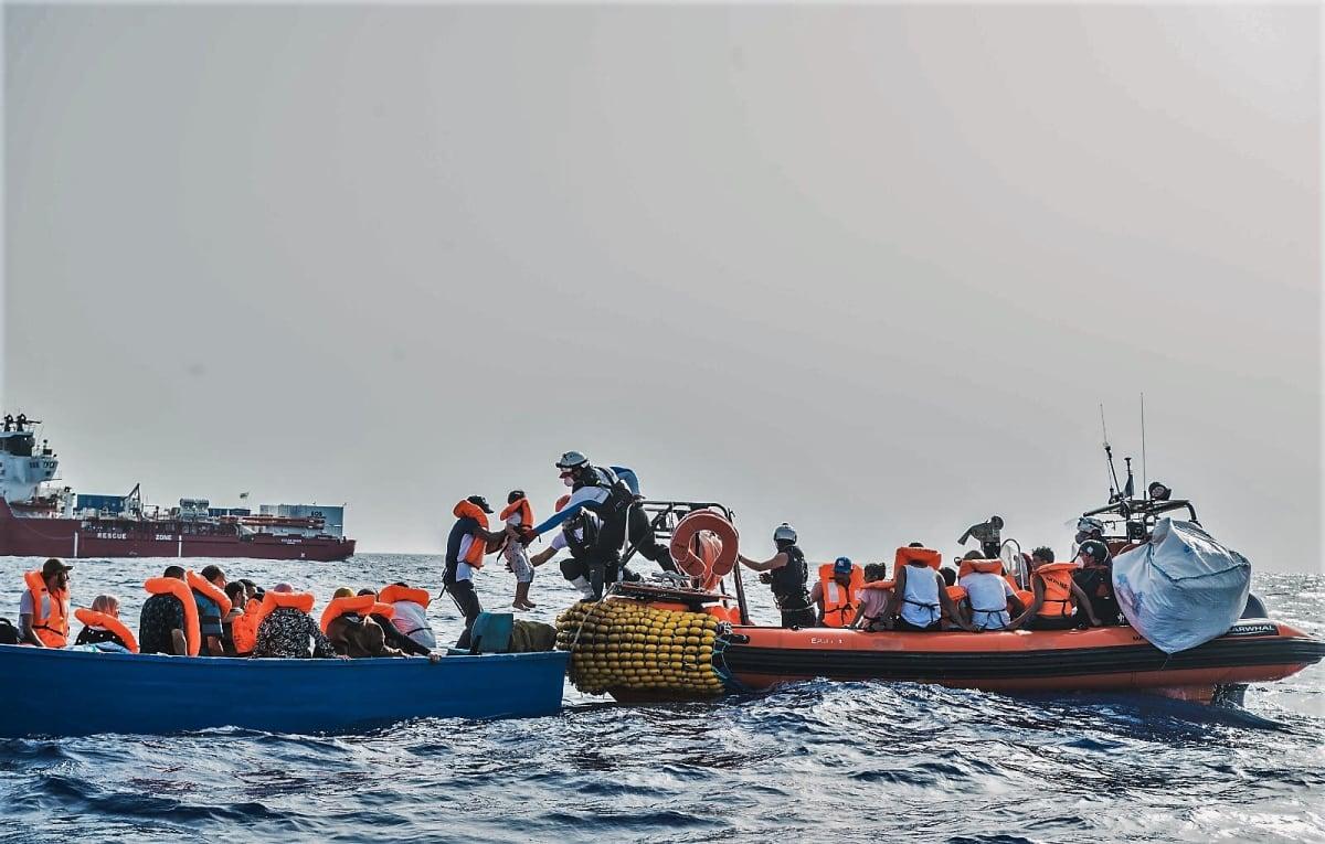 Siirtolaisia autetaan sinisestä veneestä oranssireunaiseen kumiveneeseen. Sukelluspukuinen mies ottaa juuri vastaan lasta. Taustalla näkyy punavalkoinen Ocean Viking -alus.