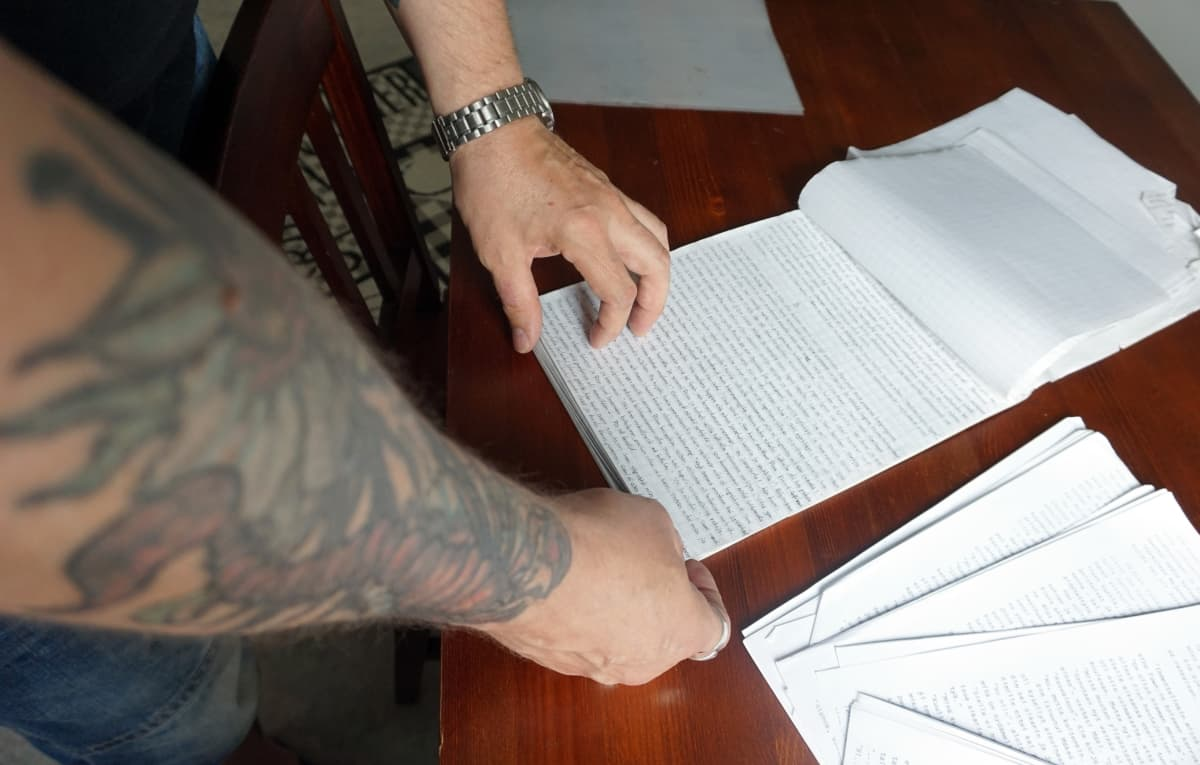 Tatuoitu käsi selaa lehtiötä