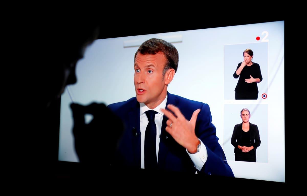 Emmanuel Macron puhuu televisioruudulla.