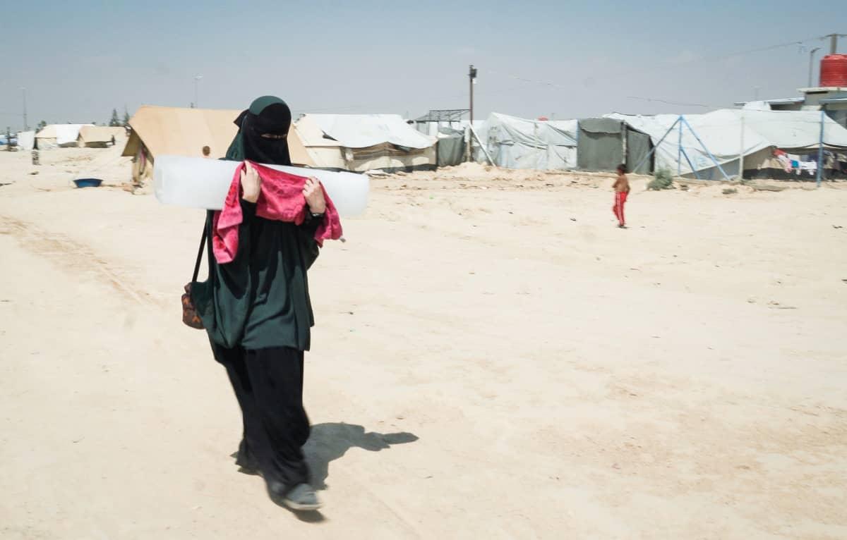 Nainen kantaa jäälohkaretta al-Holin leirissä Syyria