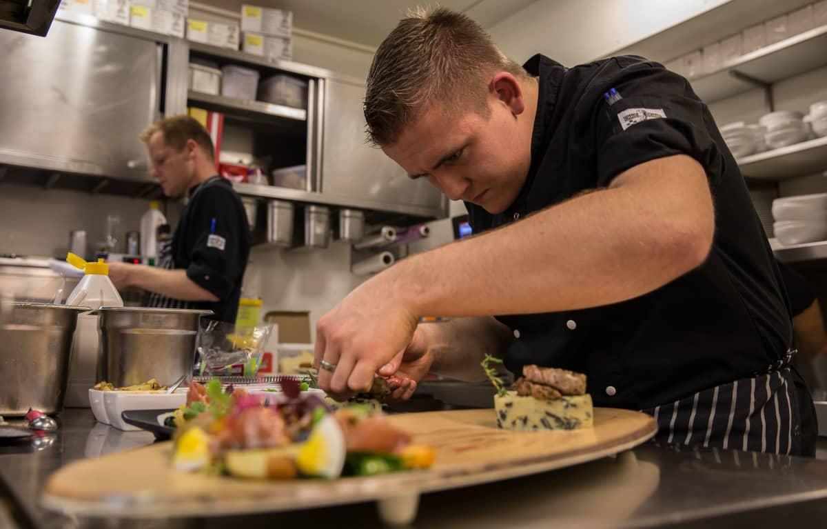 Kokki viimeistelee annoksia ravintolan keittiössä.