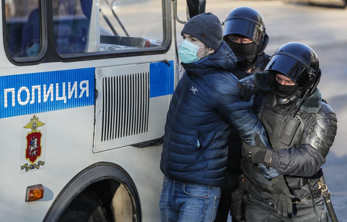 Aleksei Navalnyi kannattaja otetaan kiinni oikeustalo ulkopuolella poliisien toimesta.