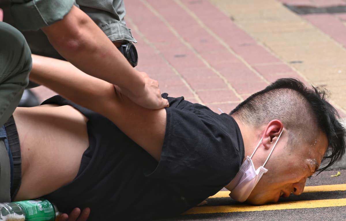 Poliisi painaa miestä vasten katua.