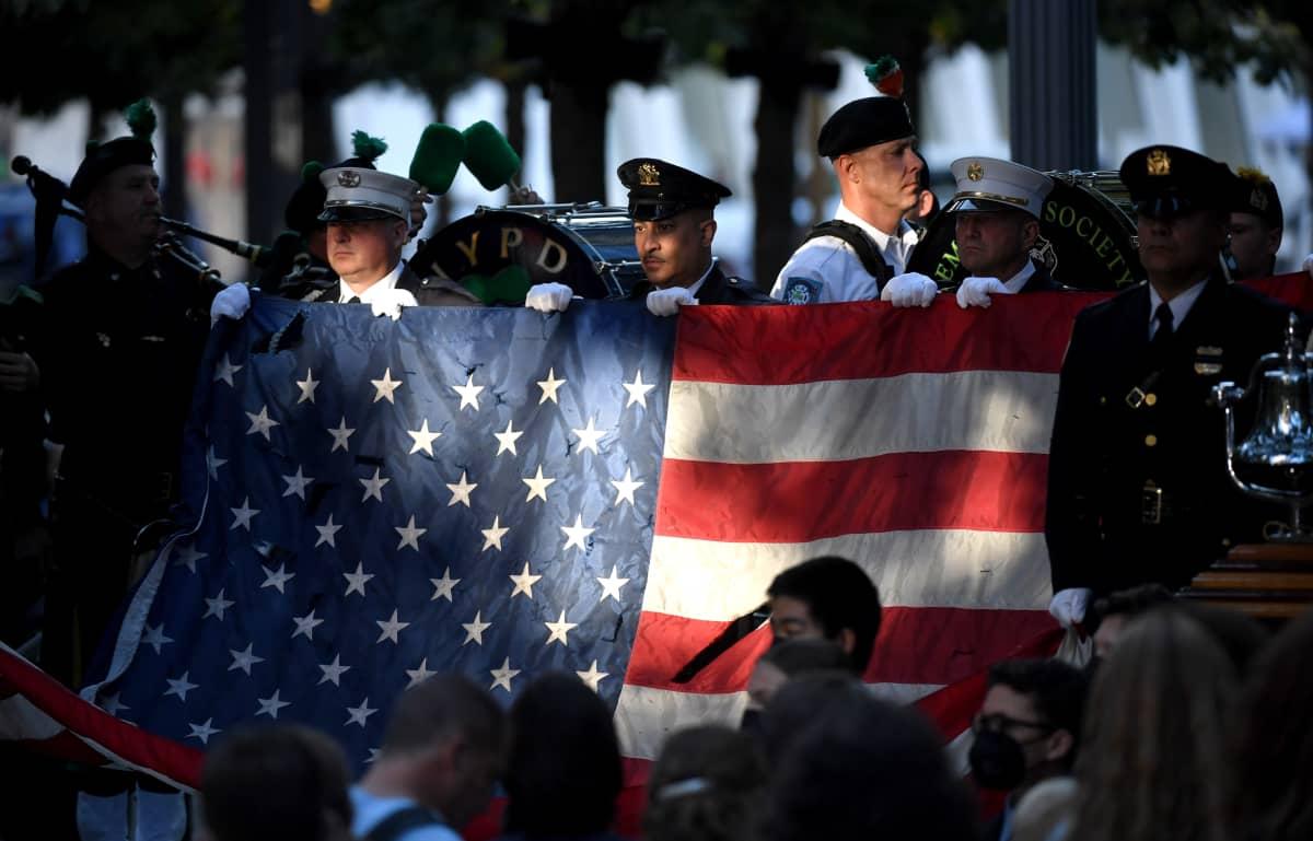 New Yorkissa poliiseja ja palomiehiä kannattelemassa Yhdysvaltojen kansallislippua. 20 vuoden takaisten tapahtumien muistotilaisuuden aluksi kuultiin Yhdysvaltojen kansallishymni.