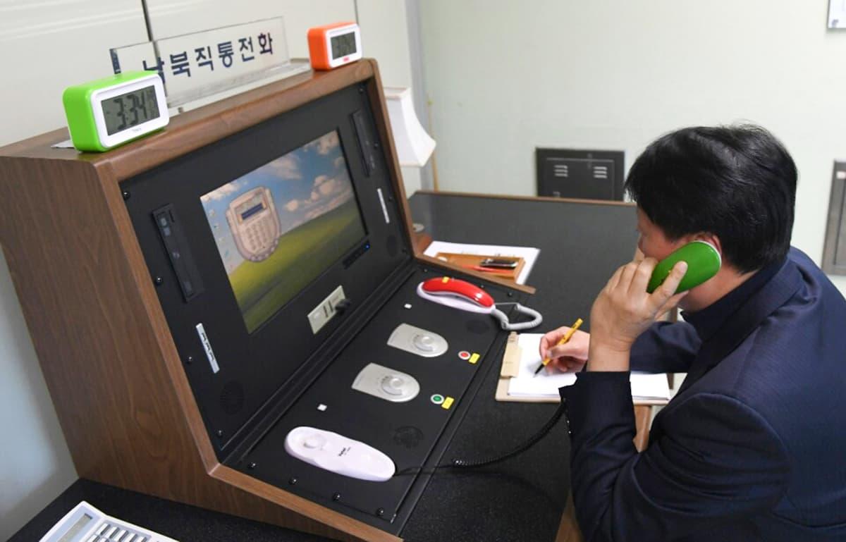 Eteläkorelaisella miehellä vihreän värinen puhelimenluuri korvallaan.