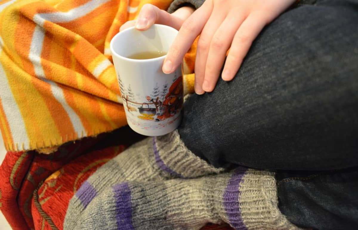 Nainen pitelee teekuppia ja istuu tuolissa.