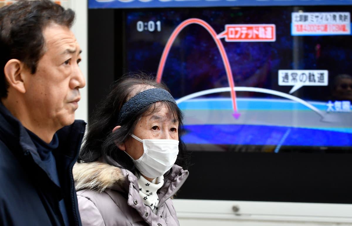 Kaksi Etelä Korealaista kävelee kadulla, taustalla iso televisionäyttö.