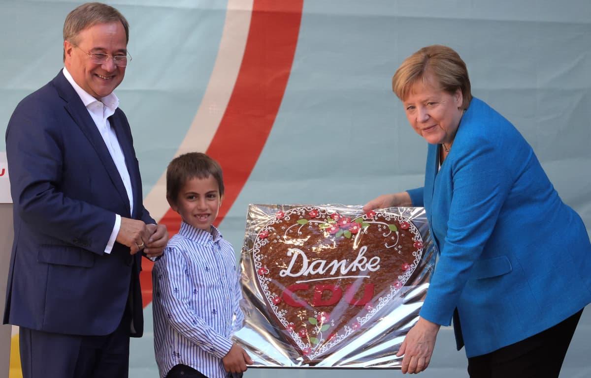 Merkel ja Laschet vastaanottavat piparin.