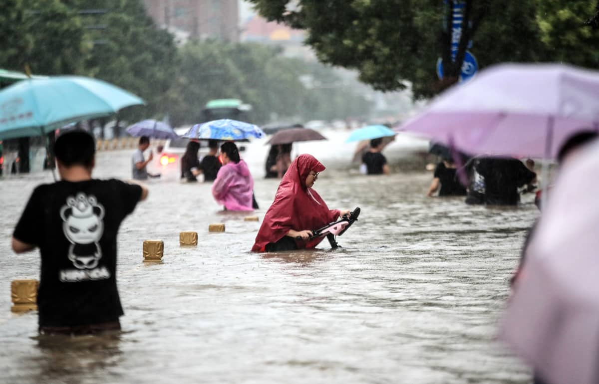 Ihmisiä kävelee vyötäröä myöten tulvivalla kadulla keski-Kiinassa.