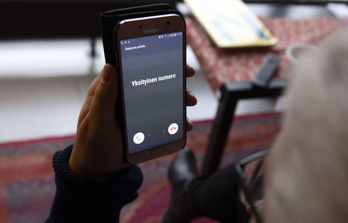 Nainen katsoo puhelimen näyttöä.