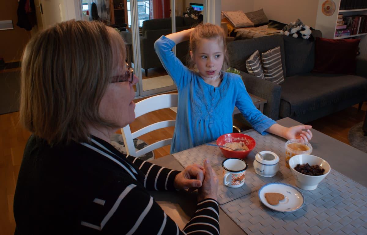 Seija Vahvelainen istuu tyttärentyttärensä kanssa ruokapöydässä.