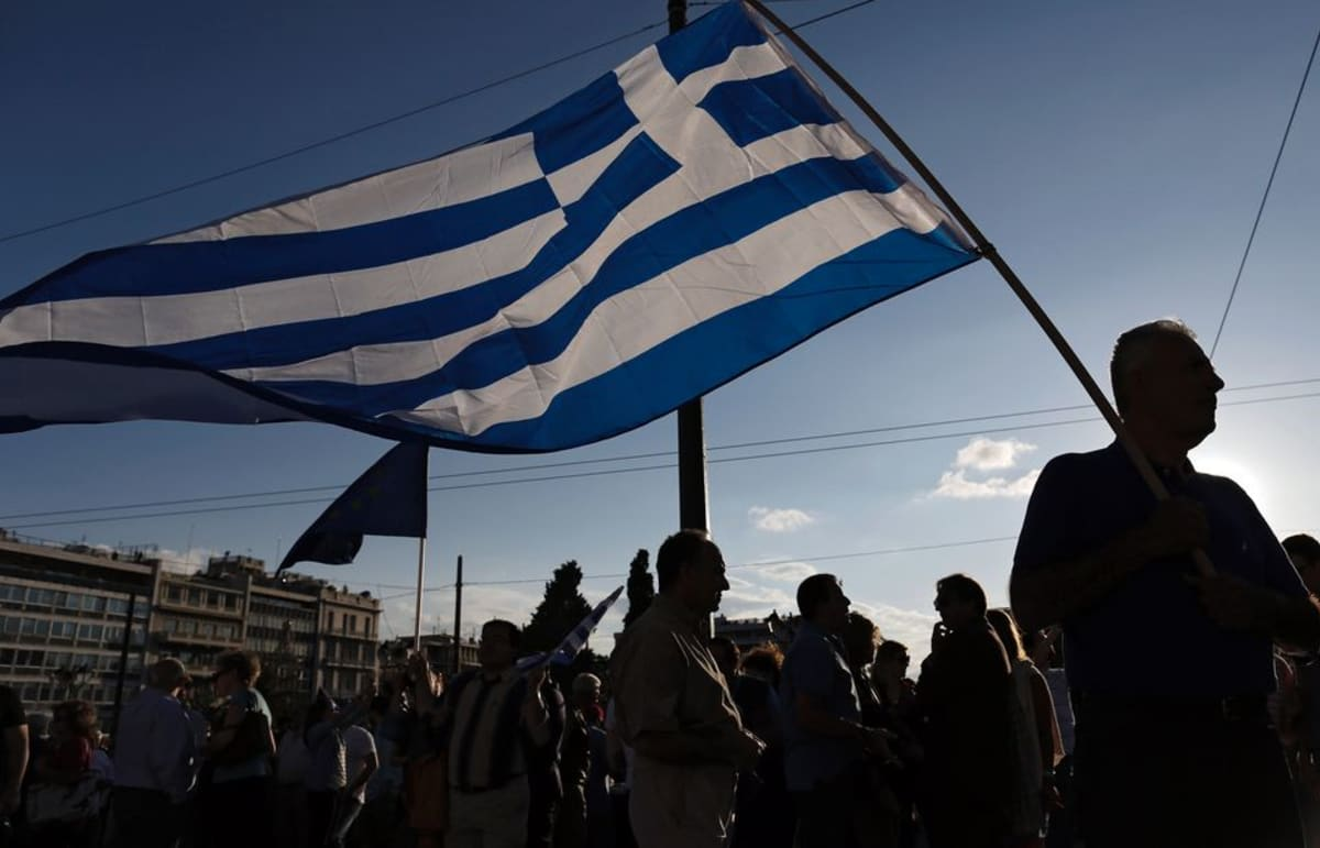 Mielenosoittajat kantavat Kreikan lippua.
