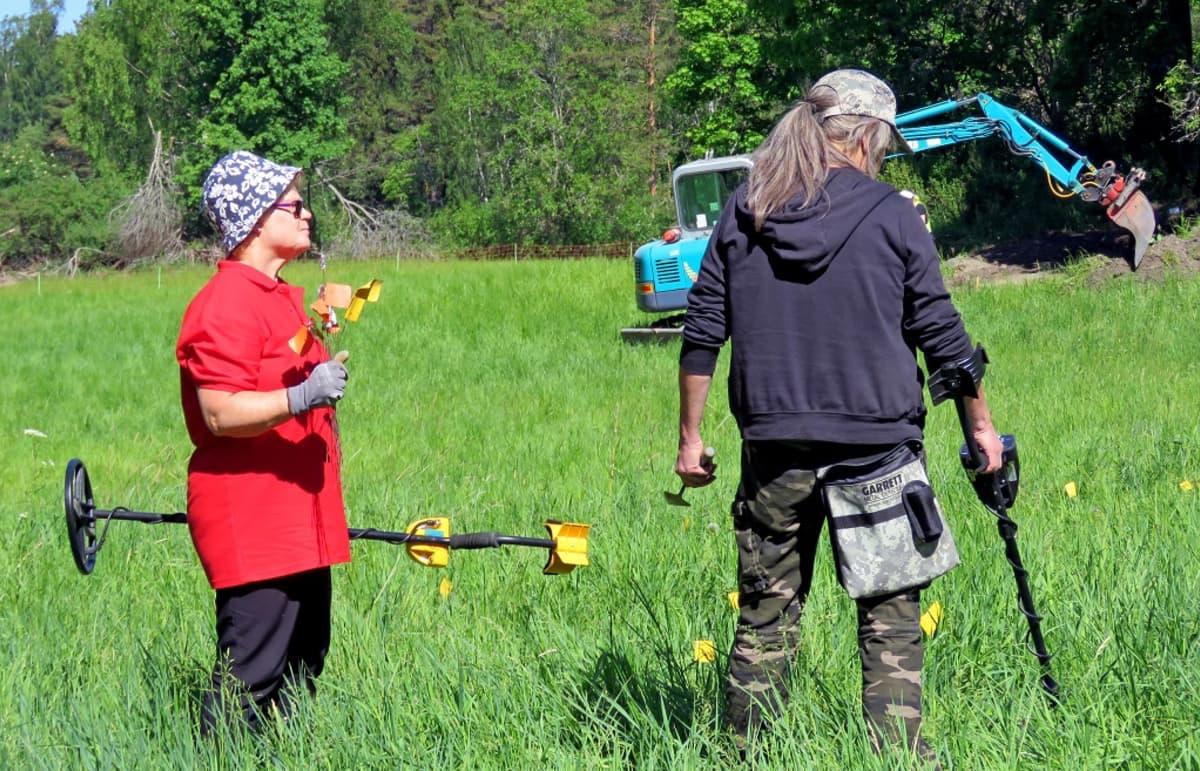 Kaksi naista metallinilmaisimineen ruohikossa. Taustalla kaivinkone.