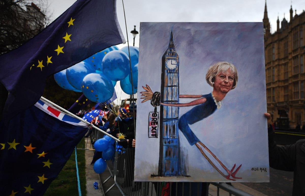 Uuden kansanäänestyksen kannattajat osoittivat mieltään Lontoon kaduilla maanantaina. Poliittinen taiteilija Kaya Mar pitelee tekemäänsä maalausta, jossa brexit on sitonut Theresa Mayn kädet Big Beniin.