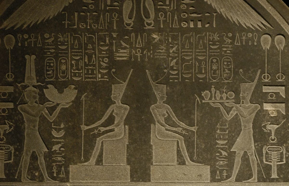Egyptiläisiä hierglyfejä ja ihmishahmoja kivitaulussa.