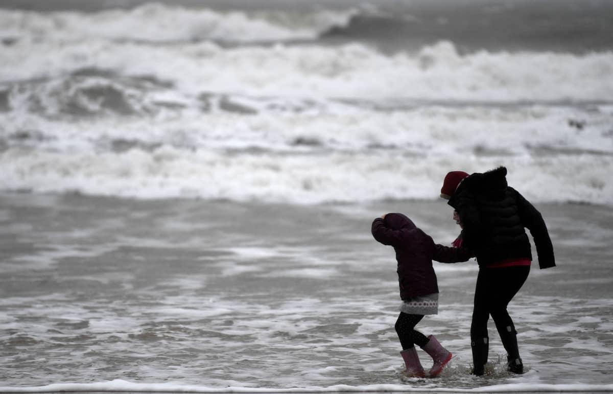 Aikuinen ja lapsi kävelevät kovassa tuulessa rannalla. Taustalla myrskyävä meri.