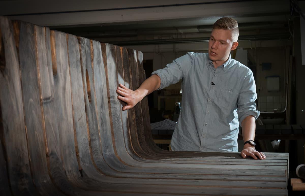 Mies tunnustelee rakenteilla olevaa saunan laudetta