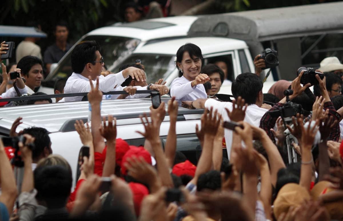Kuvassa Aung San Suu Kyi heiluttaa kannattajilleen auton kattoikkunan kautta.