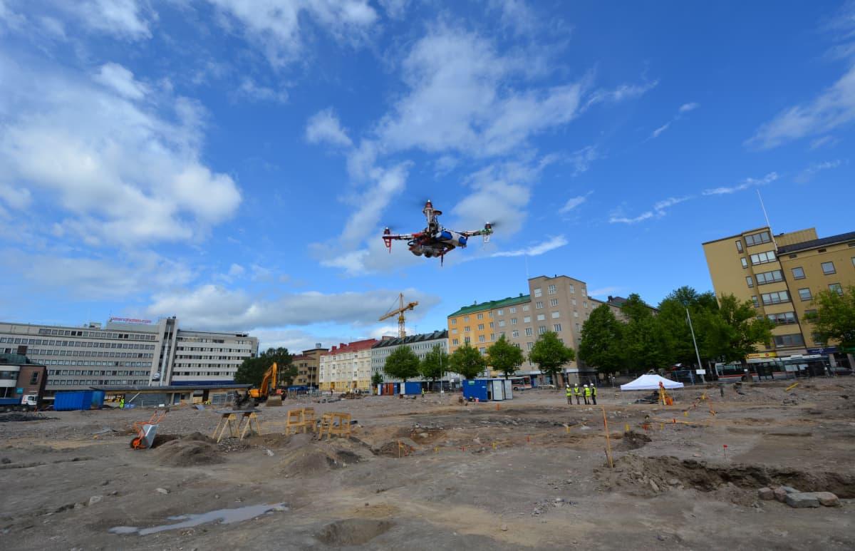 Radio-ohjattava helikopteri kuvaa Lahden torin työmaata.