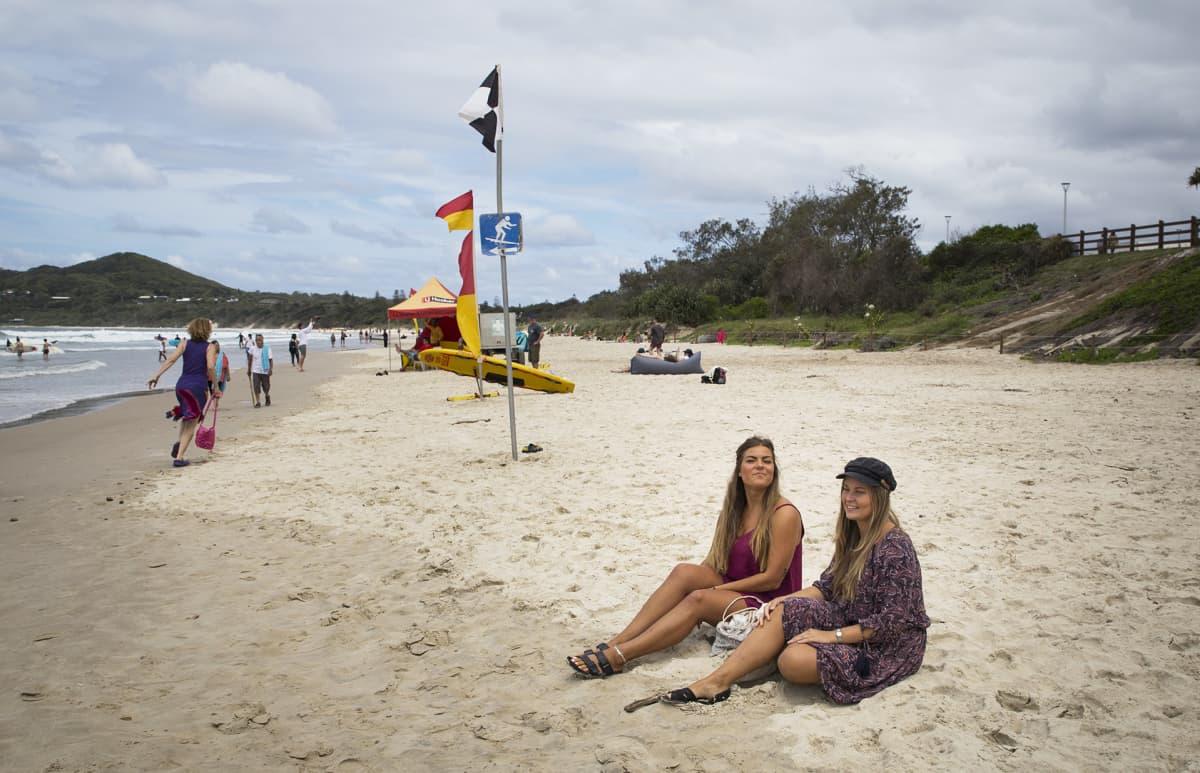 Sofia Klouvatos ja Miisa Mäensyrjä istuvat kuvassa hiekkarannalla.